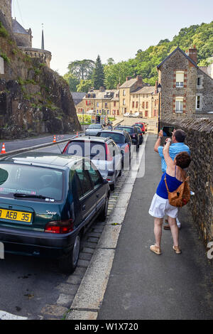 Tourists in Fougères taking photos with ipad and phone of the castle - Stock Image