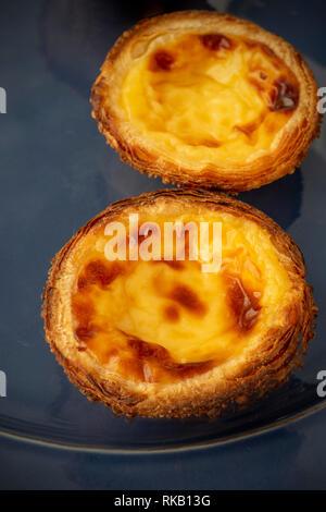 Two Portuguese Egg Tarts Pastel de Nata On. Blue Plate - Stock Image