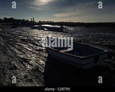Dinghies lie on the mud beside a creek in Norfolk,England. - Stock Image