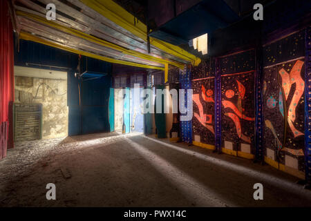 Interior view with colourful wall art in the abandoned casino at the Black Coast in Constanta, Romania. - Stock Image