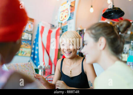 Young women friends looking at map in restaurant - Stock Image
