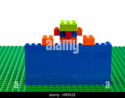Lego brick construction of a boy, man, male with jug-ears and a green cap confined behind a blue wall raising himself - Stock Image