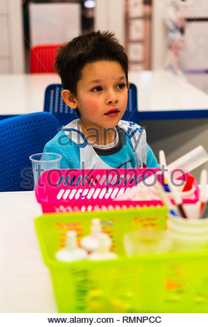 Poznan, Poland - February 2, 2019: Young boy listening and sitting by a table during experiment class in a university. - Stock Image