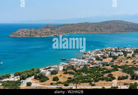 Plaka, Crete, Greece. June 2019. An overview of the seaside resort of Plaka and the former Leper Colony on Spinalonga Island. - Stock Image