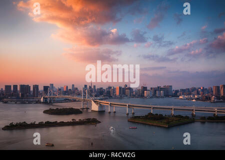 Tokyo skyline with Tokyo Tower and Rainbow Bridge at sunset in Tokyo, Japan - Stock Image