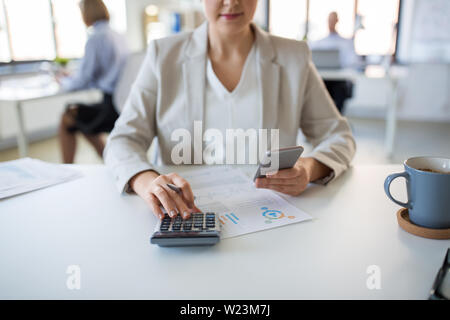 businesswoman with calculator and smartphone - Stock Image