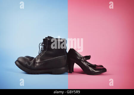 A man's boots and woman's high heels are against a blue and pink isolated background for a struggle or gender - Stock Image