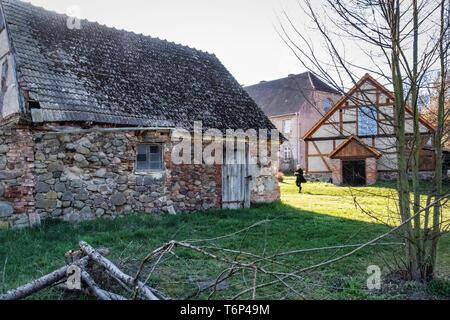 Derelict old barn building with stone exterior and half timbered tudor-style facade on Gutshaus Manor House estate,Friedenfelde,Gerswalde, Brandenburg - Stock Image