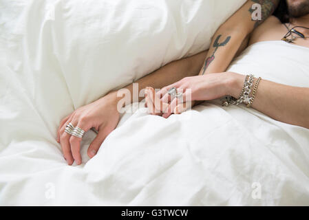 A young tattooed couple draping their arms across a duvet. - Stock Image