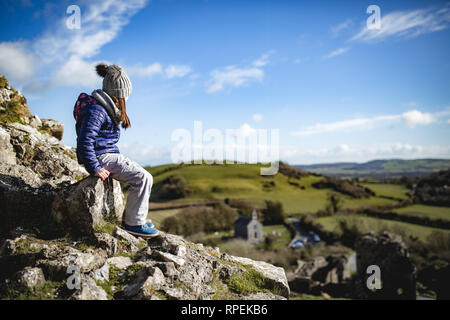 Girl sitting on the ruins of The Rock of Dunamase popular historic attraction located outside Portlaoise, County Laois, Ireland - Stock Image
