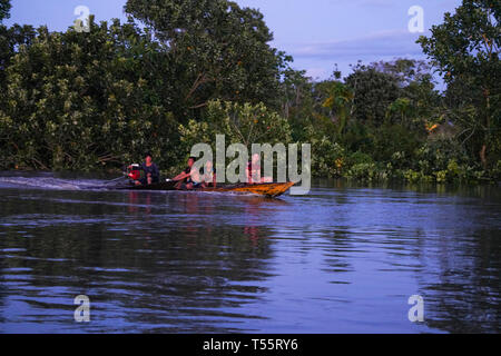 Traditional wooden motor canoe cruising the Amazon during super moon - Stock Image