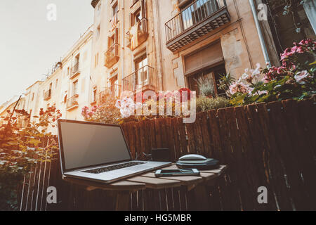 Small cozy beautiful workspace on balcony with laptop on wooden table, mouse, smartphone and a lot of flowers around - Stock Image