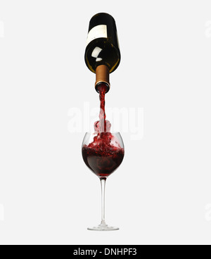 A bottle of red wine pouring into a glass from above. - Stock Image