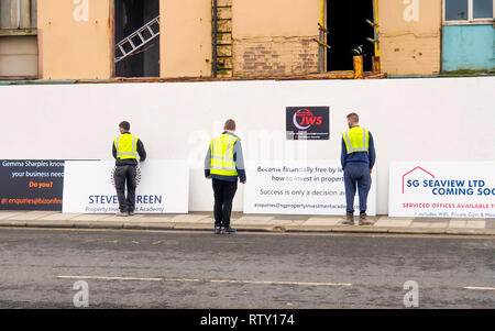 Three men preparing to erect advertising signs for a property development trying to work out how they should be assembled - Stock Image