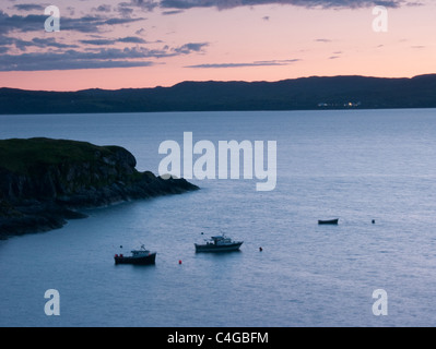 Three boats at sunset in the Sound of Sleat, Scotland. The distant shore is the Isle of Skye - Stock Image