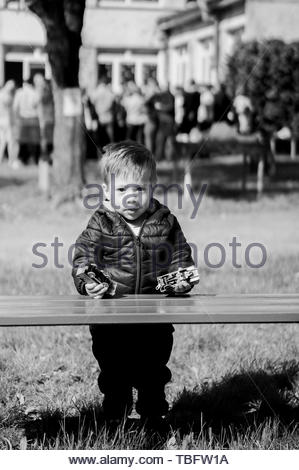Young boy standing by a wooden bench holding two - Stock Image
