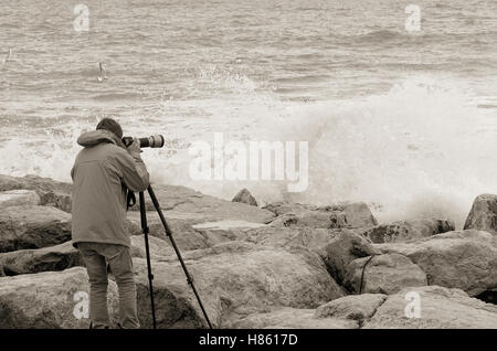photographer over the cliff with stormy sea - Stock Image