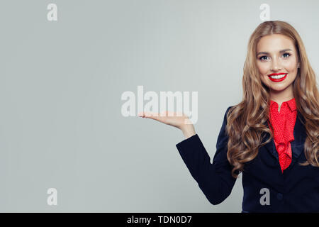 Student woman showing open hand with empty palm on white background - Stock Image