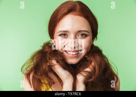 Image of a beautiful happy young redhead girl posing isolated over green wall background. - Stock Image