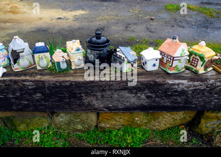A row of old fashioned fancy teapots some damaged used as ornaments in a garden by the sea on the Yorkshire Coast - Stock Image