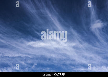 Wispy white clouds against a bright blue summer sky. - Stock Image