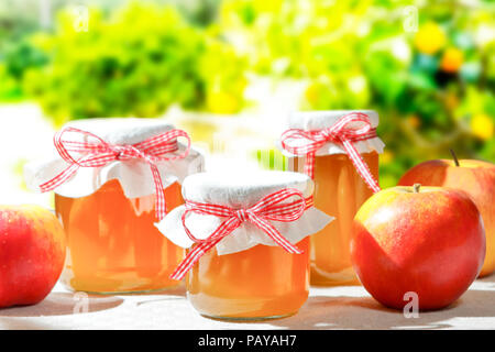 Homemade apple jelly in glass jars with linen cover and a nostalgic ribbon bow in bright sunshine with apple trees in the background - Stock Image
