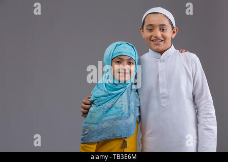 Young Muslim girl and boy holding each other and smiling - Stock Image