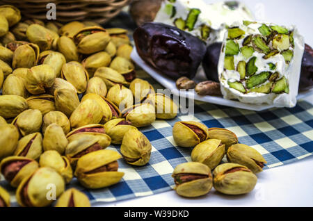 White plate with persimmon and nougat next to fried pistachios on blue square paper - Stock Image