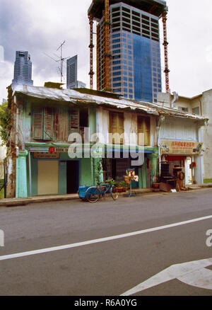 Boon Tat Street in Singapore 1976 contrasting with new skyscrapers under construction in background. Vintage street scene typical of Singapore in 1970' - Stock Image