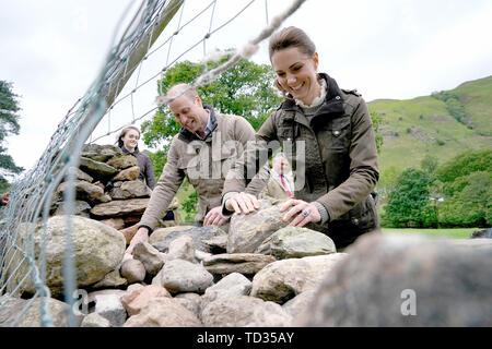 The Duke and Duchess of Cambridge laugh as they take part in the repair of a dry stone wall at Deepdale Hall Farm, a traditional fell sheep farm, in Patterdale, during a visit to Cumbria. - Stock Image