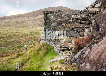 Moel Hebog and overhanging wall above old tram lines in Gorseddau slate quarry in Snowdonia National Park. Cwmystradllyn Porthmadog Gwynedd Wales UK - Stock Image