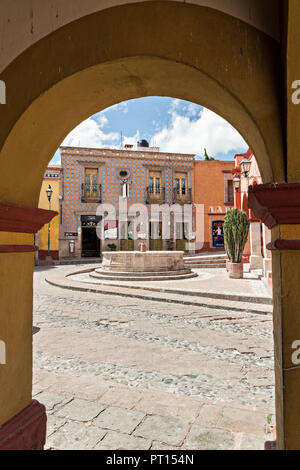 View through an archway of the Bernal public fountain at Zaragoza and Hidalgo streets in the beautiful colonial village of Bernal, Queretaro, Mexico. Bernal is a quaint colonial town known for the Pena de Bernal, a giant monolith which dominates the tiny village is the third highest on the planet. - Stock Image