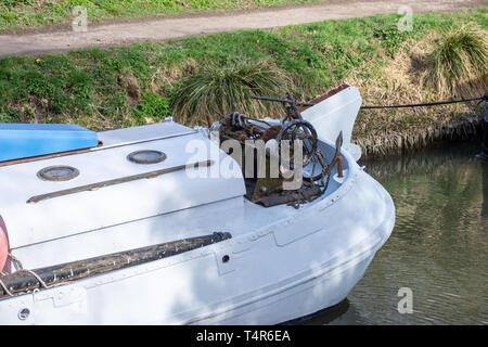 The stern of a river sailing boat with an old vintage rusty hand winch and anchor on the Kennet and Avon canal in Bradford on Avpn Wiltshire. - Stock Image