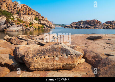 Mountain with boulders and river at Hampi, the centre of the Hindu Vijayanagara Empire in Karnataka state in India - Stock Image