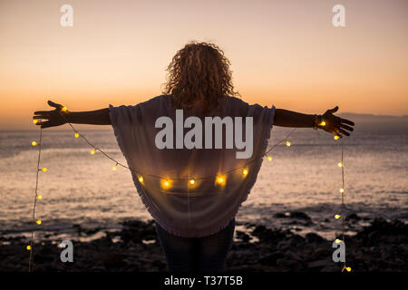 Enjoying freedom and nature concept with curly blonde woman viewed from back with open arms to hug the nature and ocean during romantic vacation and t - Stock Image
