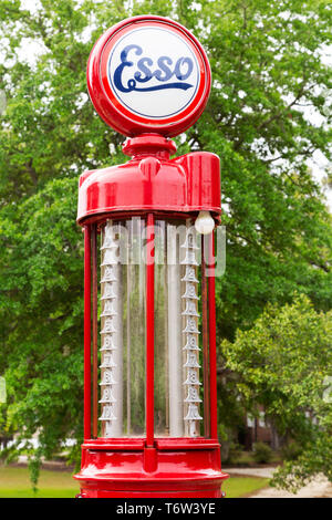 A vintage petrol pump in South Carolina, USA. The nozzle hangs from the red metal pump. - Stock Image