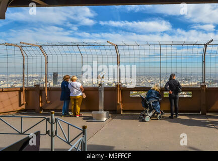 Tourists including a woman in a wheelchair enjoy the city view of Paris on a sunny day from the first platform of - Stock Image