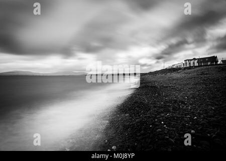 A fantastic north atlantic landscape on a moody irish day. The town houses overlook the rocky beach and the ocean. - Stock Image