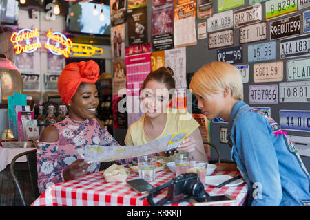 Young women friends looking at map on vacation in bar - Stock Image