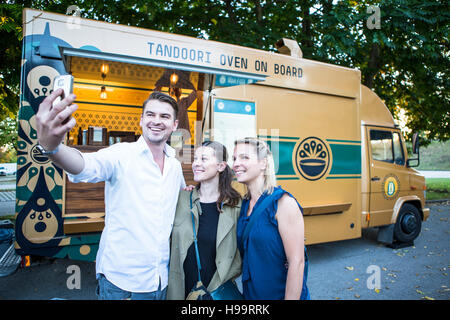 Customers taking a selfie next to food truck - Stock Image