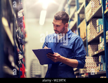 auto mechanic with clipboard at car workshop - Stock Image