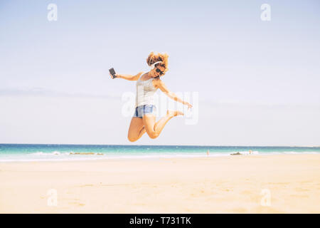People happines concept for summer holiday vacation leisure activity at the beach - young crazy beautiful blonde woman jump with phone and headphones  - Stock Image