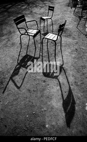 Paris France. Chairs in the Jardin du Luxembourg. 2000 The Jardin du Luxembourg, also known in English as the Luxembourg Gardens, is located in the 6th arrondissement of Paris, France. It was created beginning in 1612 by Marie de' Medici, the widow of King Henry IV of France, for a new residence she constructed, the Luxembourg Palace. The garden today is owned by the French Senate, which meets in the Palace. It covers 23 hectares and is known for its lawns, tree-lined promenades, flowerbeds, model sailboats on its circular basin, and picturesque Medici Fountain, built in 1620. - Stock Image