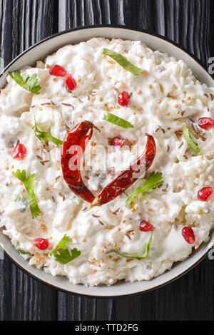 Indian Curd rice with carrots, pomegranate and with additional tempering of spices close-up in a plate on the table. Vertical top view from above - Stock Image