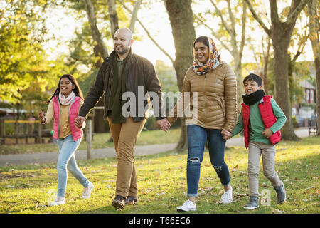 Muslim family holding hands, walking in autumn park - Stock Image