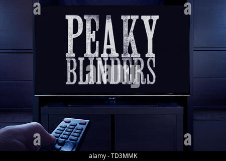 A man points a TV remote at the television which displays the Peaky Blinders main title screen (Editorial use only). - Stock Image