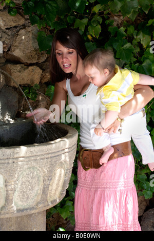 Mother Toddler drinking water from fountain Mijas Pueblo, Costa del Sol, Andalucia, Spain - Stock Image