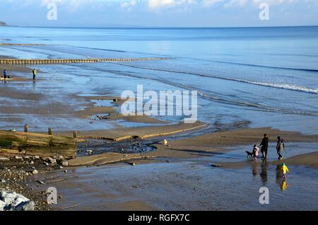 Couple walking with children and dogs on Amroth Beach in winter Carmarthenshire Wales Cymru UK - Stock Image