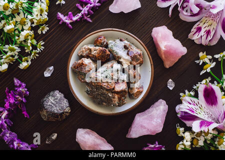 Garnet with Rose Quartz and Mixed Flowers on Dark Table - Stock Image