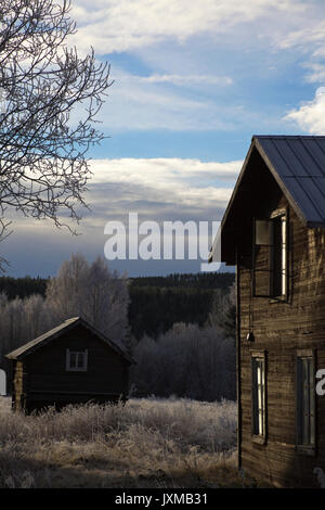 Wooden house with broken window on a frosty autumn morning in Sweden. - Stock Image